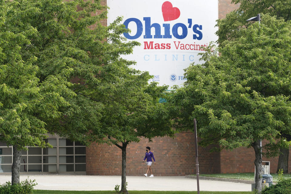 FILE - In this May 25, 2021, file photo, a man walks by the entrance for Ohio's COVID-19 mass vaccination clinic at Cleveland State University in Cleveland. Ohio plans to announce its third pair of Ohio Vax-a-Million winners Wednesday evening, June 9, 2021, even as the initial bump from the incentive program fades and the vaccination numbers continue to drop. (AP Photo/Tony Dejak, File)