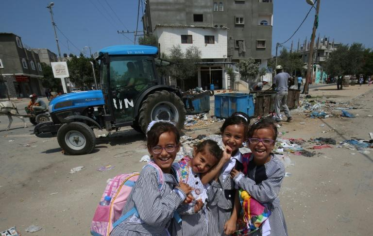 Palestinian schoolgirls pose near a UN Relief and Works Agency (UNRWA) tractor in Rafah refugee camp in the Gaza Strip, on September 1, 2018 following Washington's announcement it was ending all funding
