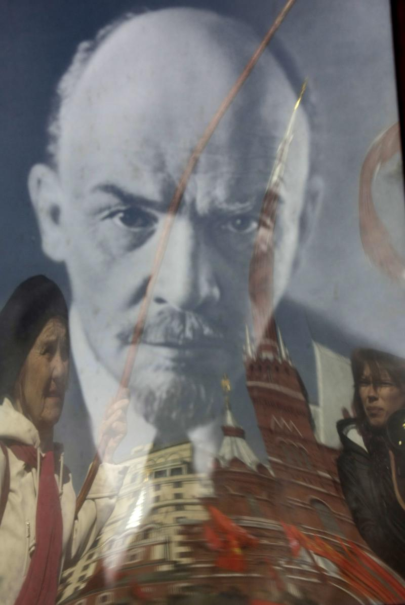 Russian communist supporters are reflected in a portrait of the Soviet founder Vladimir Lenin as they stand in a queue in Red Square, Moscow, to visit the Mausoleum to mark the 141st anniversary of Lenin's birth, Friday, April 22, 2011. (AP Photo/Mikhail Metzel)