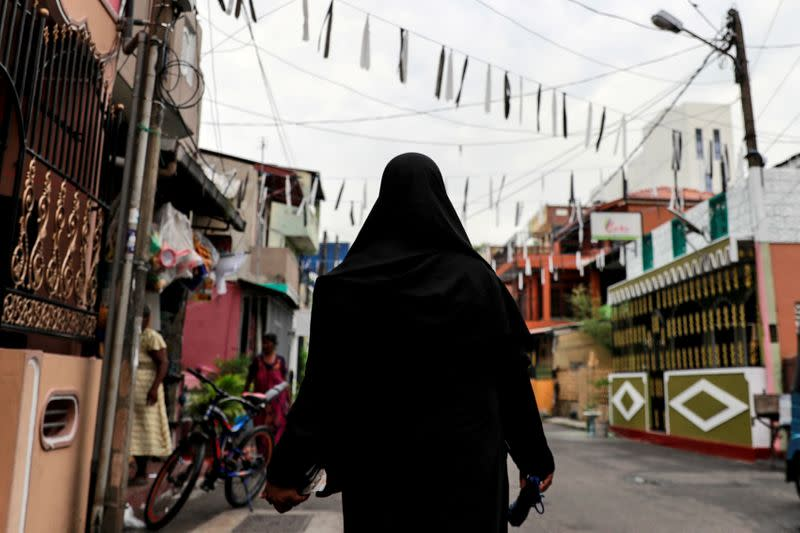 FILE PHOTO: A Muslim woman wearing a hijab walks through a street near St Anthony's Shrine in Colombo