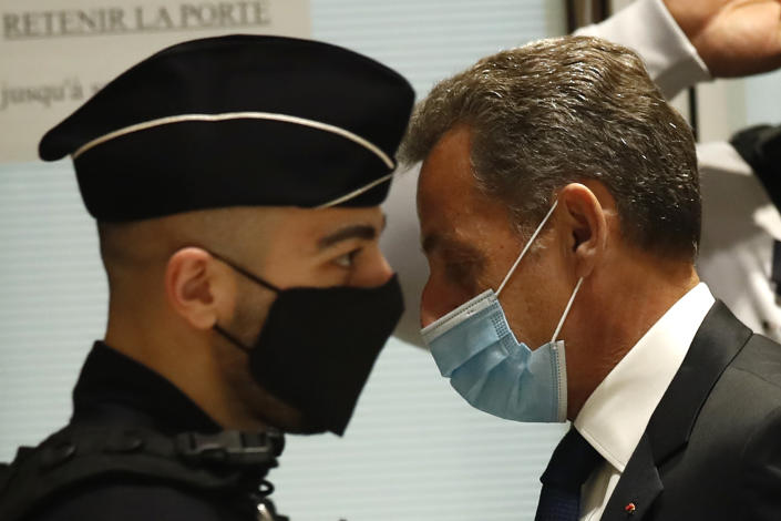 Former French President Nicolas Sarkozy, right, arrives at the courtroom in Paris Monday, March 1, 2021. The verdict is expected in a landmark corruption and influence-peddling trial that has put French former President Nicolas Sarkozy at risk of a prison sentence if he is convicted. Sarkozy, who was president from 2007 to 2012, firmly denied all the allegations against him during the 10-day trial that took place at the end of last year. (AP Photo/Michel Euler)