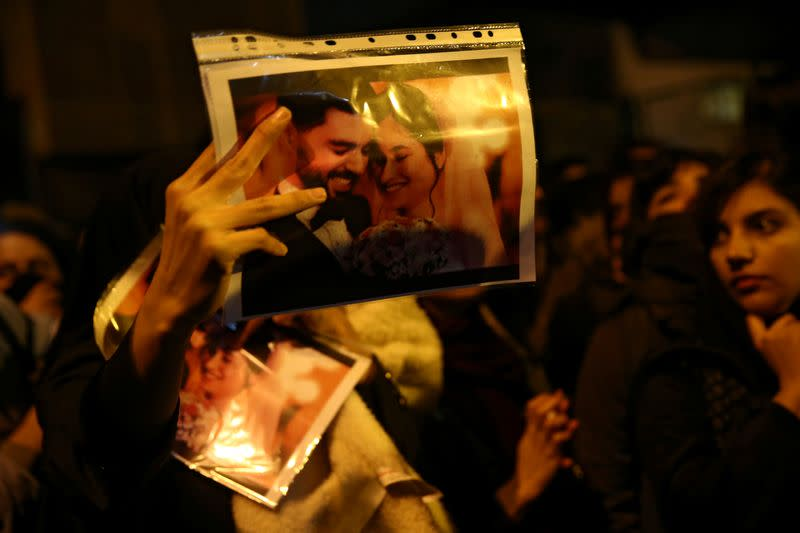 FILE PHOTO: A woman holds a picture of newlyweds, victims of the crash of the Boeing 737-800 plane, flight PS 752, as people gather to show their sympathy in Tehran