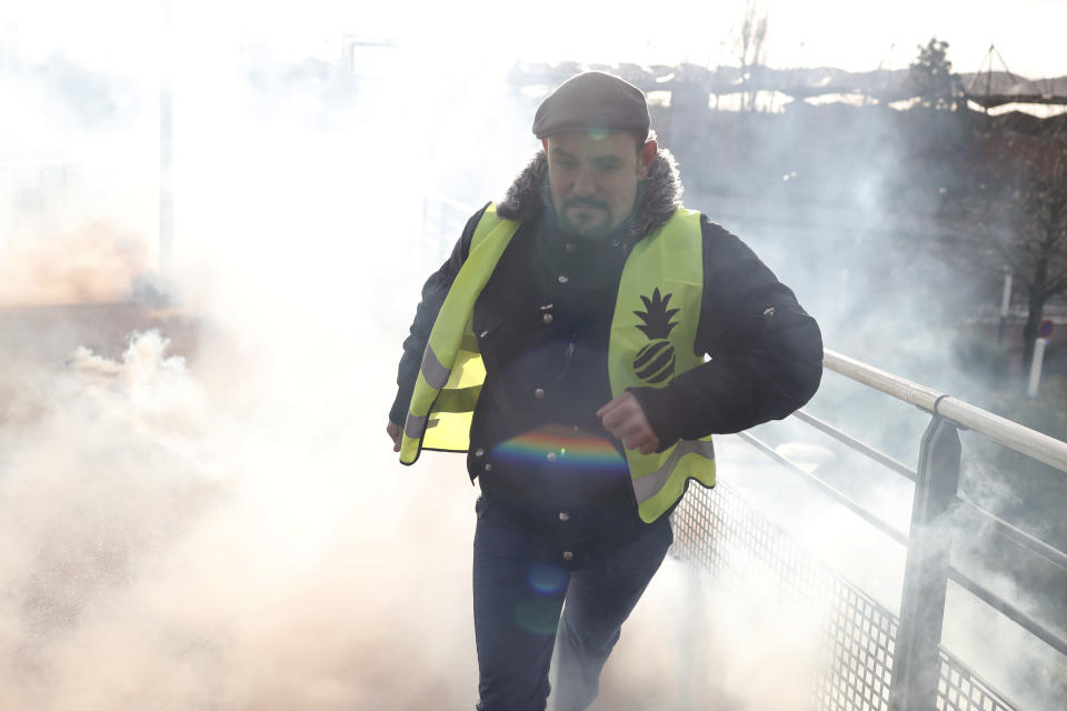 A protestor runs from teargas launched by riot police during a demonstration of unionist and yellow vests, in Creteil, outside Paris, Wednesday, Jan. 9, 2019. About 200 protesters, including unionists and yellow vests, gathered Wednesday in Creteil, a Paris suburb, as Macron was doing a visit in a facility dedicated to handball. Some scuffles broke out with police forces that used tear gas to keep the crowd at a distance from the French leader. (AP Photo/Thibault Camus)