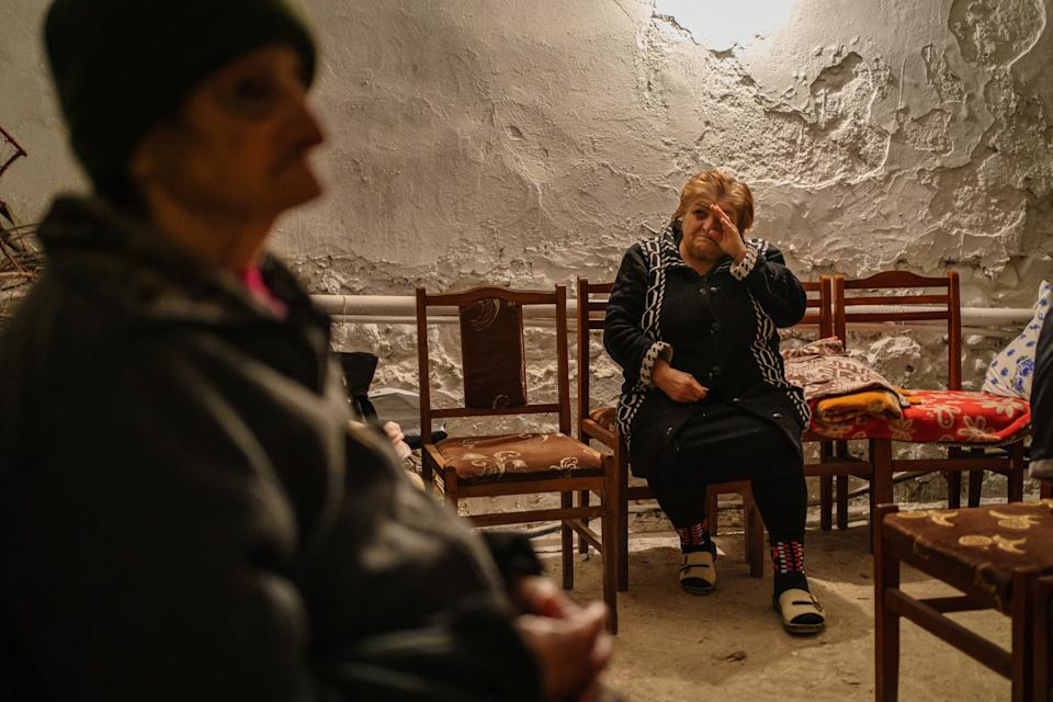 A woman in a chair, right, weeps as she and another resident take shelter in a basement in Nagorno-Karabakh.