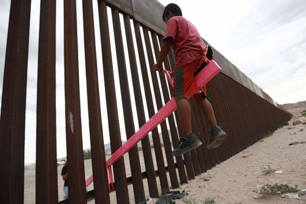 PHOTO: A child plays on a seesaw installed between the border fence that divides Mexico from the United States in Ciudad de Juarez, Mexico, July 28, 2019. The seesaw was designed by Ronald Rael, a professor of architecture in California. (Christian Chavez/AP)