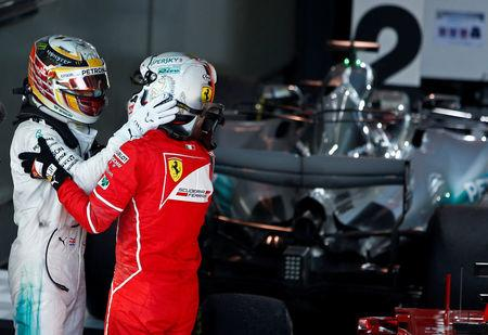 Formula One - F1 - Australian Grand Prix - Melbourne, Australia - 26/03/2017 - Ferrari driver Sebastian Vettel of Germany is congratulated by Mercedes driver Lewis Hamilton of Britain after winning the Australian Grand Prix.     REUTERS/Brandon Malone