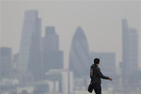 A man walks through Greenwich Park as a haze of pollution sits over the London skyline