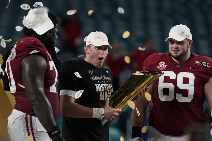 Alabama quarterback Mac Jones, middle, offensive linemen Alex Leatherwood, left, and Landon Dickerson, right, celebrate with the trophy, after their win against Ohio State in an NCAA College Football Playoff national championship game, Tuesday, Jan. 12, 2021, in Miami Gardens, Fla. Alabama won 52-24. (AP Photo/Chris O'Meara)