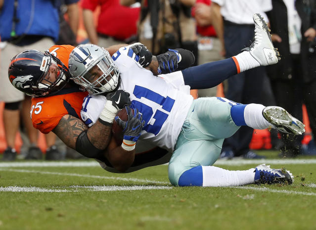 Ezekiel Elliott is tackled by Broncos cornerback Chris Harris during the second half of the Cowboys' 42-17 loss. (AP)