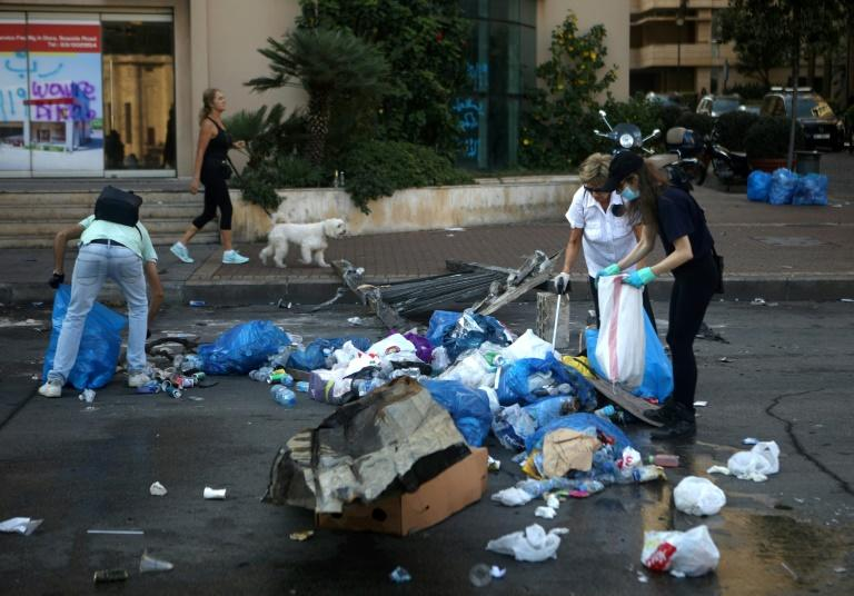 Lebanese demonstrators clean up rubbish on a street in the capital Beirut's downtown district following a night of protests against tax increases and official corruption (AFP Photo/Patrick BAZ)