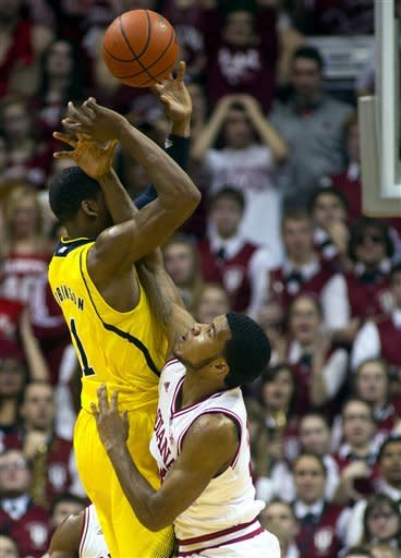 Michigan's Glenn Robinson III (1) is fouled by Indiana's Jeremy Hollowell (33) as he takes a shot during the second half of an NCAA college basketball game Saturday, Feb. 2, 2013, in Bloomington, Ind. Indiana defeated Michigan 81-73. (AP Photo/Doug McSchooler)