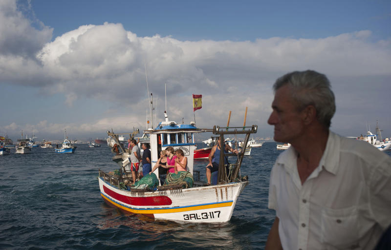 Fishermen on their fishing boats try to reach Gibraltar as British and Spanish patrol boats, unseen, block their access during a protest near to La Linea de la Concepcion in front of Gibraltar, Spain, Sunday, Aug. 18, 2013. Spanish fishermen in some 60 fishing boats are protesting against the building of an artificial reef near the disputed British territory of Gibraltar, which has also soured relations between Madrid and London. The fishermen say the reef of around 70 concrete blocks, some with steel rods protruding, can snare their nets. (AP Photo/Laura Leon)
