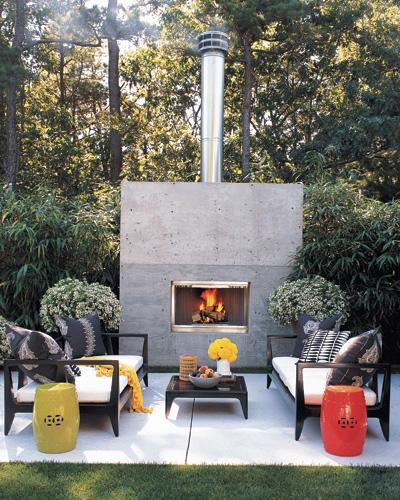 Influenced by the indoor-outdoor lifestyle of Southern California and the clean-lined architecture of Tadao Ando, decorator Eric Hughes created a minimalist terrace for entertaining at his house in Wainscott, N.Y. The furniture has a modern Asian look, amplified by a pair of colorful ceramic stools from Mecox Gardens; the fireplace wall is poured concrete.  (Photo: Roger Davies)