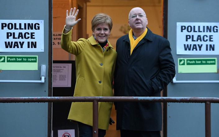 Scotland's First Minister and leader of the Scottish National Party (SNP), Nicola Sturgeon, stands with her husband husband Peter Murrell as they stand outside a Polling Station where she arrived to cast her ballot paper and vote, in Glasgow, Scotland, on December 12, 2019 - AFP