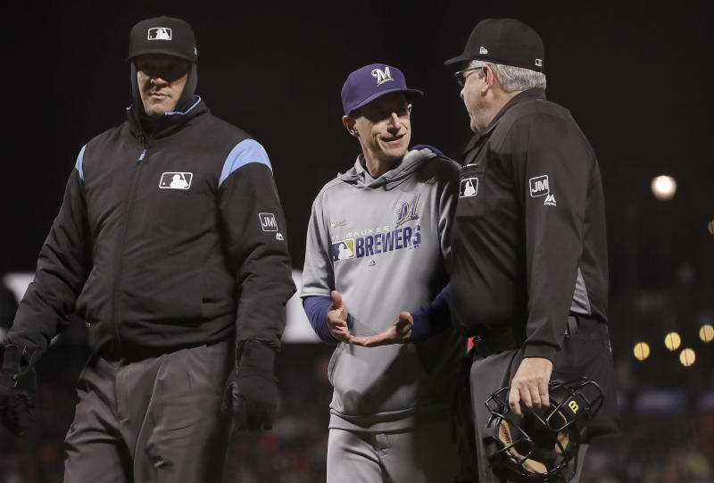 Milwaukee Brewers manager Craig Counsell, center, talks with umpires Chad Fairchild, left, and Paul Emmel before challenging a call that San Francisco Giants' Kevin Pillar was safe stealing second base during the seventh inning of a baseball game in San Francisco, Friday, June 14, 2019. The ruling was upheld. (AP Photo/Jeff Chiu)