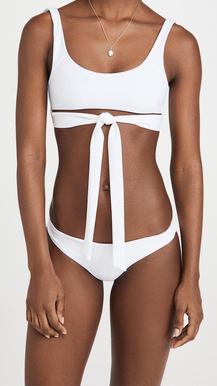 """<p><strong>Jade Swim</strong></p><p>shopbop.com</p><p><strong>$120.00</strong></p><p><a href=""""https://go.redirectingat.com?id=74968X1596630&url=https%3A%2F%2Fwww.shopbop.com%2Fbond-top-jade-swim%2Fvp%2Fv%3D1%2F1597552961.htm&sref=https%3A%2F%2Fwww.oprahdaily.com%2Fstyle%2Fg36166852%2Fbest-swimsuits-for-small-busts%2F"""" rel=""""nofollow noopener"""" target=""""_blank"""" data-ylk=""""slk:SHOP NOW"""" class=""""link rapid-noclick-resp"""">SHOP NOW</a></p><p>Wrap details are a big swim trend and this scoop neckline happens to complement small boobs.</p>"""