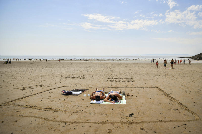 People sunbathe in a marked out square in the sand, indicating two meters, on Barry Island beach, in Wales, Friday, July 31, 2020. First Minister for Wales, Mark Drakeford, has announced that from Monday up to 30 people can meet outside while maintaining social distancing in the latest easing of coronavirus measures in Wales. (Ben Birchall/PAvia AP)