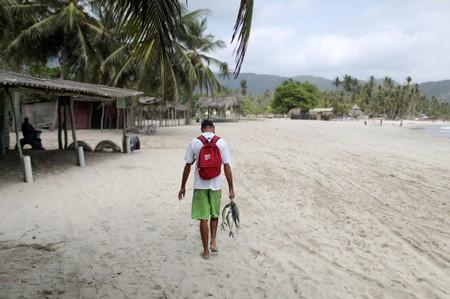A fisherman walks along a beach carrying fish used as a means of payment, in Patanemo