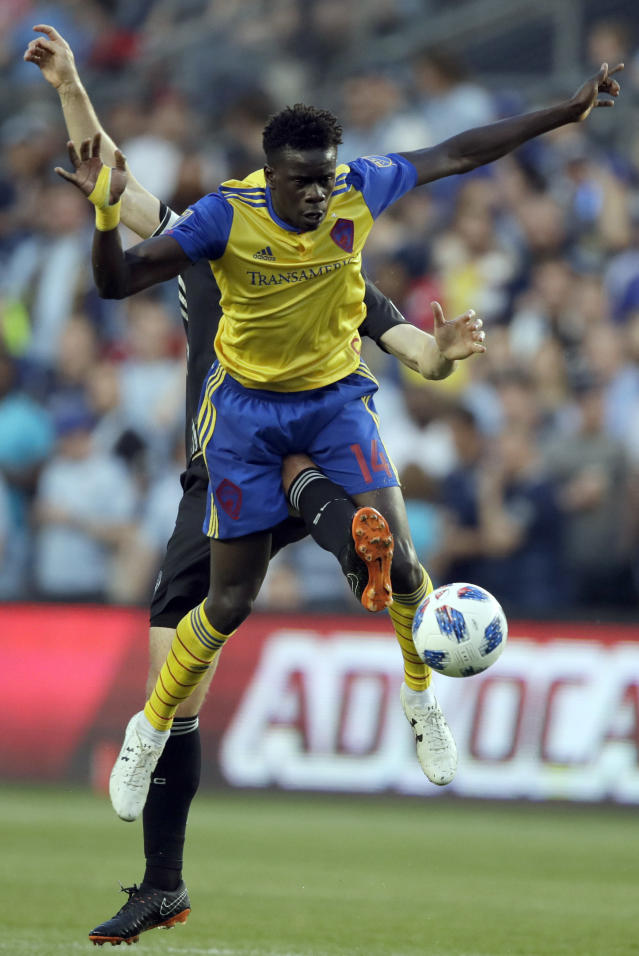 Sporting Kansas City defender Matt Besler, back, tries to get to the ball past Colorado Rapids forward Dominique Badji (14) during the first half of an MLS soccer match in Kansas City, Kan., Saturday, May 5, 2018. (AP Photo/Orlin Wagner)