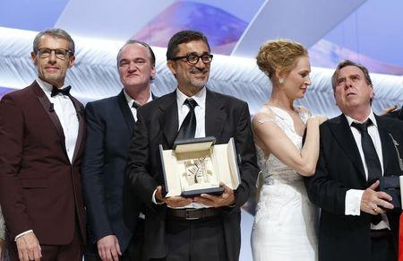 "(L-R) Master of Ceremony actor Lambert Wilson, director Quentin Tarantino, director Nuri Bilge Ceylan, Palme d'Or award winner for his film ""Winter Sleep"", actress Uma Thurman, and actor Timothy Spall, Best Actor award winner for his role in the film ""Mr. Turner"", pose on stage during the closing ceremony of the 67th Cannes Film Festival in Cannes May 24, 2014. REUTERS/Yves Herman"