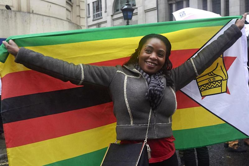 A woman holds a Zimbabwe flag on The Strand (AFP/Getty Images)