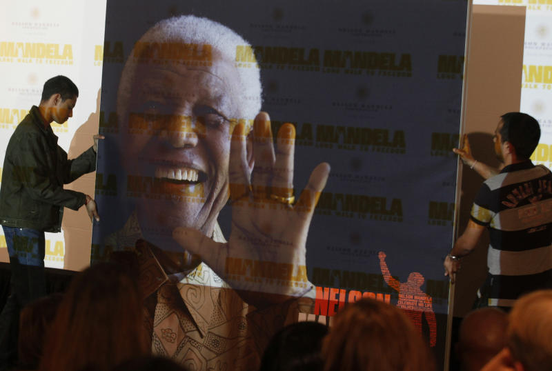 """FILE - In this Nov. 2, 2013 file photo, a giant poster of Nelson Mandela is moved to center stage at a news conference held to promote the newly released film """"Mandela: Long Walk To Freedom,"""" in Johannesburg. The ailing former president is not """"doing well"""" but is continuing to put up a courageous fight from his """"deathbed,"""" members of his family have told the South African Broadcasting Corporation in an interview. (AP Photo/Denis Farrell, File)"""