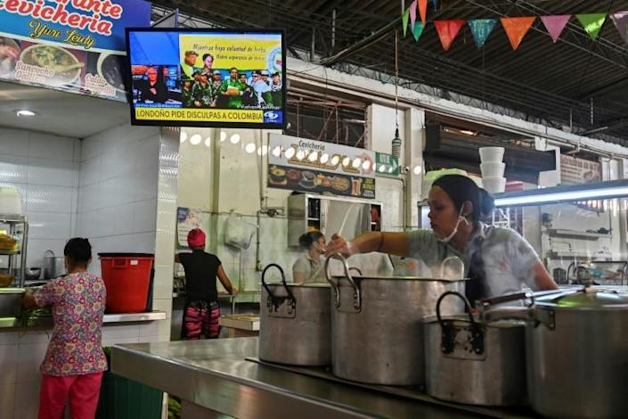 A TV in a market in Cali, Colombia, broadcasts a video posted on YouTube on August 29, 2019 of former senior commander Ivan Marquez and fellow rebel Jesus Santrich announcing that they are taking up arms again (AFP Photo/Luis ROBAYO)