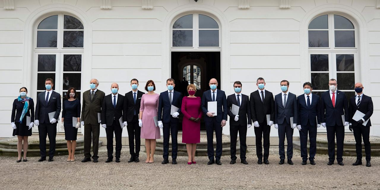 TOPSHOT - Newly appointed Slovak Prime Minister Igor Matovic (C-L), leader of the OLaNO anti-graft party and President Zuzana Caputova (C-R) pose for a family picture with Ministers after a swearing in ceremony of the new four-party coalition government on March 21, 2020 outside of the Presidential palace in Bratislava. - The ceremony was held without members of the press and all appointed government members wore gloves and face mask to prevent the spread of novel coronavirus. (Photo by JOE KLAMAR / AFP) (Photo by JOE KLAMAR/AFP via Getty Images)