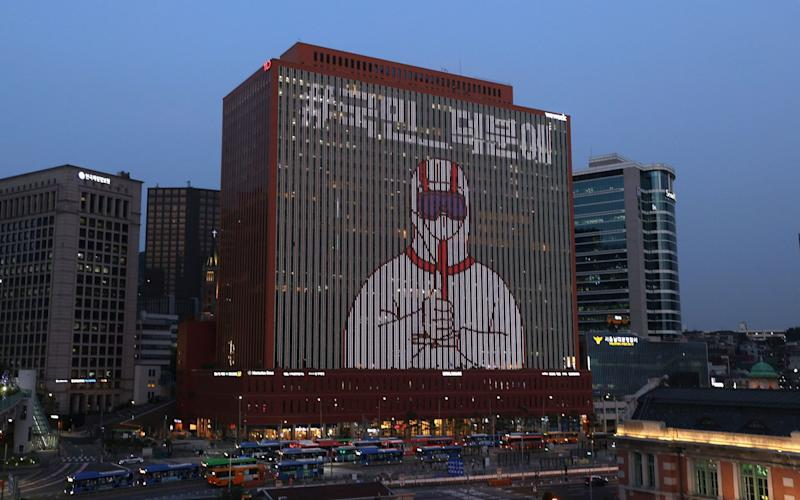 A video featuring an image of a person in protective clothing giving a thumbs-up is displayed on the wall of a building in central Seoul, south Korea - YONHAP/EPA-EFE/Shutterstock