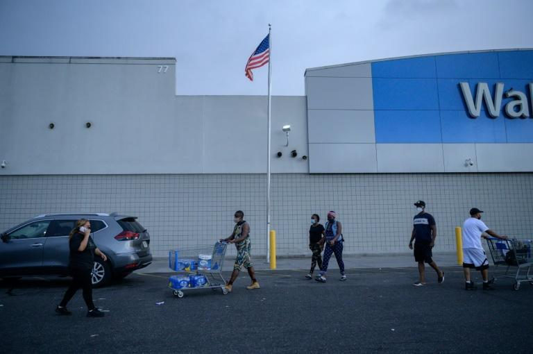 Shoppers exit a department store as tropical storm Henri approaches in Westbury, Long Island on August 21, 2021