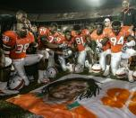 FILE - In this Nov. 23, 2006, file photo, Miami players, including Rashaun Jones (38) at left, pay their respects as they gather around a mural of teammate Bryan Pata after an NCAA college football game against Boston College in Miami. Jones was arrested Thursday, Aug. 19, 2021, in connection with the 2006 fatal shooting of his teammate Bryan Pata. Pata, a 22-year-old, 6-foot-4, 280-pound defensive lineman, was shot several times outside of his Kendall, Fla., apartment the night of Nov. 7, 2006. (Al Diaz/Miami Herald via AP)