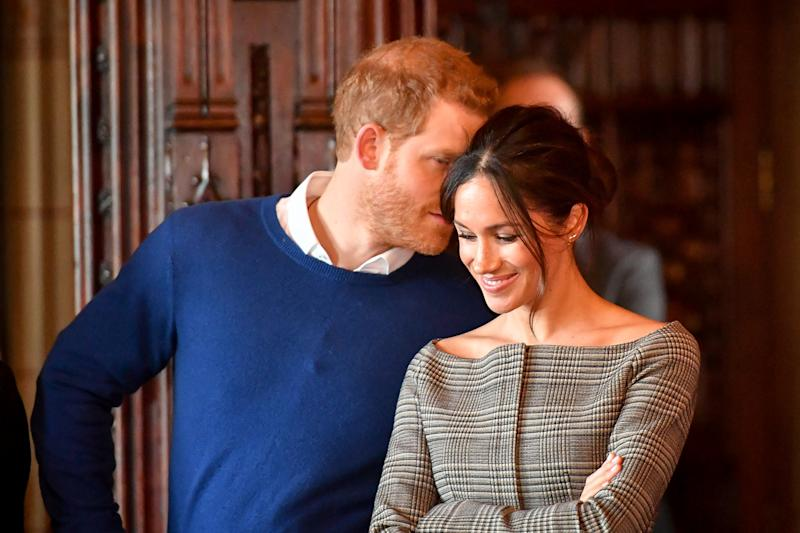 Britain's Prince Harry whispers to Meghan Markle as they watch a performance by a Welsh choir in the banqueting hall during a visit to Cardiff Castle in Cardiff, Britain, January 18, 2018. REUTERS/Ben Birchall/Pool