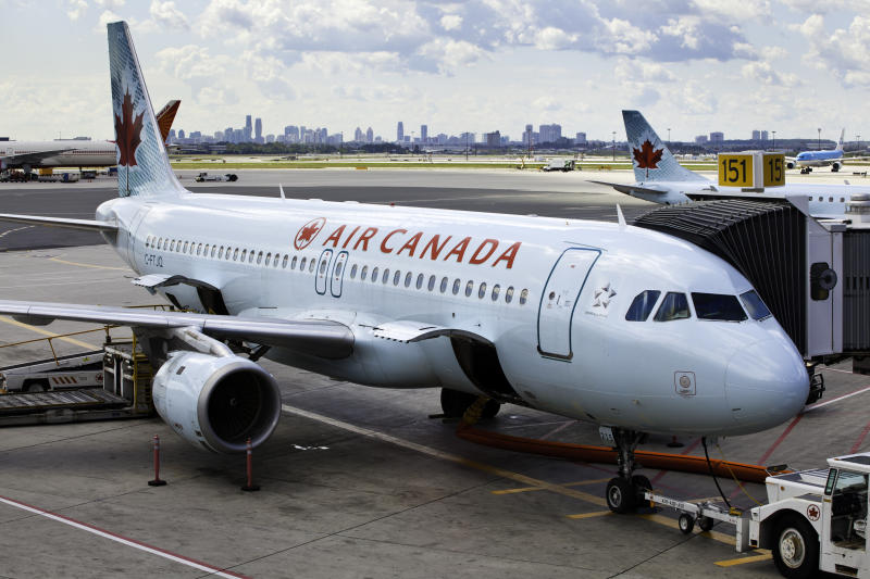 Toronto, Ontario, Canada - August 29, 2011: At Toronto Pearson International Airport, a commercial, Air Canada jet is being loaded and prepped for departure. Doors open on aircraft ready to loading baggage.