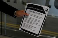 A man holds information on Thomas Cook flights at Manchester Airport