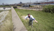 """Resident Engineer Steve Sherrill, with the US Army Corps of Engineers, shows how much height will be added to some of the levees and seawalls near a refinery Thursday, July 26, 2018, in Port Arthur, Texas. The oil industry wants the government to help protect some of its facilities on the Texas Gulf Coast against the effects of global warming. One proposal involves building a nearly 60-mile """"spine"""" of flood barriers to shield refineries and chemical plants. Many Republicans argue that such projects should be a national priority. But others question whether taxpayers should have to protect refineries in a state where top politicians still dispute whether climate change is real. (AP Photo/David J. Phillip)"""