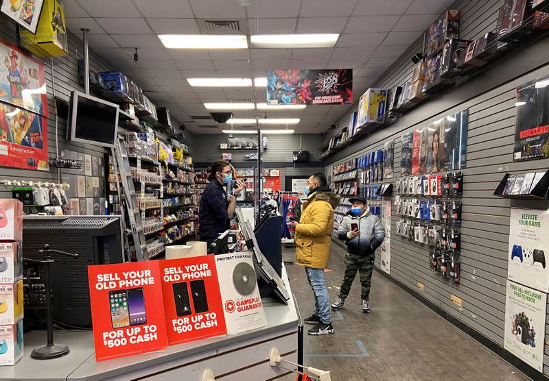 FILE PHOTO: An employee talks with a customer at a GameStop shop in New York City