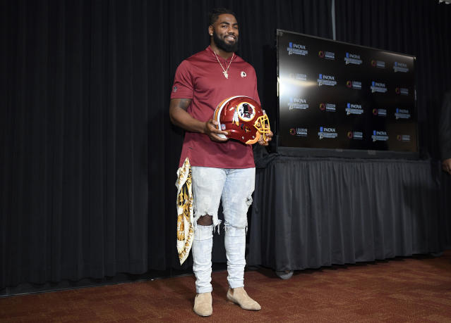 New Washington Redskins safety Landon Collins poses with a Redskins helmet before an NFL football press conference, Thursday, March 14, 2019, in Ashburn, Va. (AP Photo/Nick Wass)