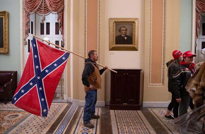 "<span class=""caption"">A historic first: the Confederate battle flag inside the U.S. Capitol.</span> <span class=""attribution""><a class=""link rapid-noclick-resp"" href=""https://www.gettyimages.com/detail/news-photo/supporter-of-us-president-donald-trump-holds-a-confederate-news-photo/1230505137"" rel=""nofollow noopener"" target=""_blank"" data-ylk=""slk:Saul Loeb/AFP via Getty Images"">Saul Loeb/AFP via Getty Images</a></span>"