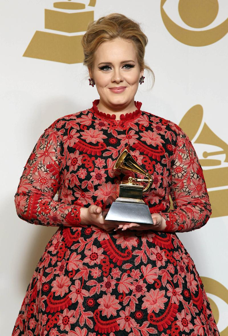"""Adele poses backstage with the award for best pop solo performance for """"Set Fire to the Rain"""" at the 55th annual Grammy Awards on Sunday, Feb. 10, 2013, in Los Angeles. (Photo by Matt Sayles/Invision/AP)"""