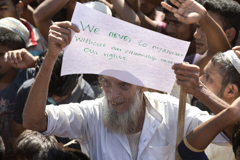 An elderly Rohingya refugee holds a placard during a protest against the repatriation process at Unchiprang refugee camp near Cox's Bazar, in Bangladesh, Thursday, Nov. 15, 2018. The head of Bangladesh's refugee commission said plans to begin a voluntary repatriation of Rohingya Muslim refugees to their native Myanmar on Thursday were scrapped after officials were unable to find anyone who wanted to return. (AP Photo/Dar Yasin)