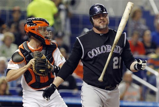 Colorado Rockies' Jason Giambi, right, tosses his bat after striking out in the second inning during a baseball game against the Miami Marlins in Miami, Wednesday, May 23, 2012. At left is Marlins catcher Brett Hayes. (AP Photo/Lynne Sladky)