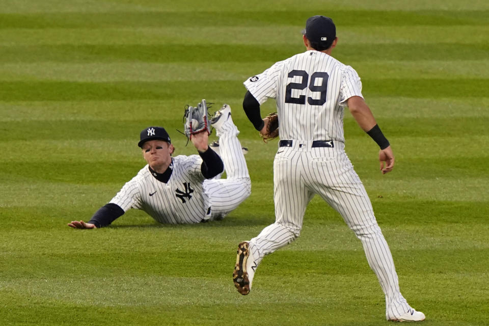 New York Yankees left fielder Clint Frazier holds the ball up after making a diving catch of a ball hit by Atlanta Braves' Ehire Adrianza during the third inning of a baseball game Wednesday, April 21, 2021, at Yankee Stadium in New York. (AP Photo/Kathy Willens)