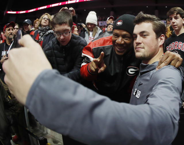 "Georgia quarterback <a class=""link rapid-noclick-resp"" href=""/ncaaf/players/264537/"" data-ylk=""slk:Jacob Eason"">Jacob Eason</a> takes a photo with a fan during media day, Saturday, Jan. 6, 2018, in Atlanta. Georgia and Alabama will be playing for the NCAA football national championship on Monday, Jan. 8. (AP Photo/John Bazemore)"