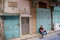 A man sits on a curb in the Christian Quarter of Jerusalem's Old City June 21, 2016. REUTERS/Ronen Zvulun