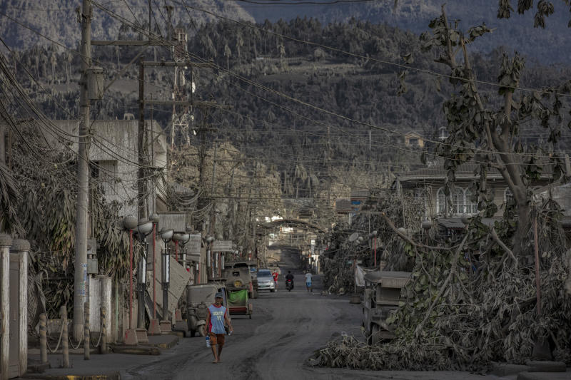 Residents walk along a road covered in volcanic ash from Taal Volcano's eruption on January 14, 2020 in Talisay, Batangas province, Philippines. (Photo: Ezra Acayan/Getty Images)