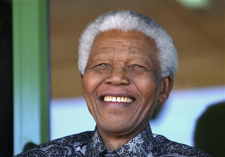 Nelson Mandela smiles as he watches the coronation ceremony of Bafokeng's King Leruo Tshekedi Molotlegi at a sports stadium in Phokeng, 120 km (81 miles) north of Johannesburg, in this August 16, 2003 file photo. REUTERS/Thomas White/Files