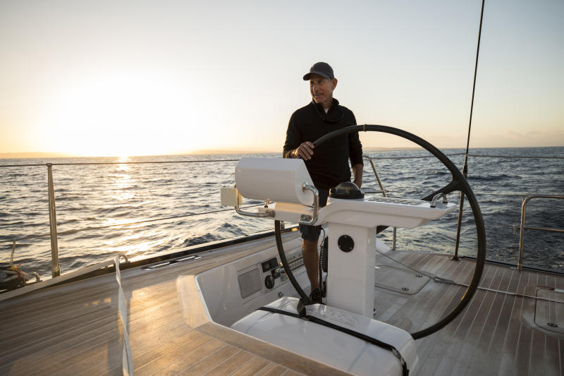 A man sailing a beautiful yacht on the open ocean.