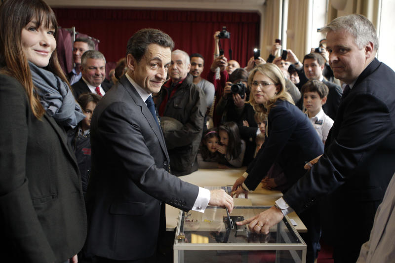 French President and UMP candidate Nicolas Sarkozy, center left, casts his vote for the second round of the presidential elections as his wife Carla Bruni-Sarkozy, left, looks on in Paris Sunday May 6, 2012. The election could see Socialist challenger Francois Hollande defeat incumbent Sarkozy by capitalizing on public anger over the government's austerity policies. (AP Photo/Michel Euler, Pool)