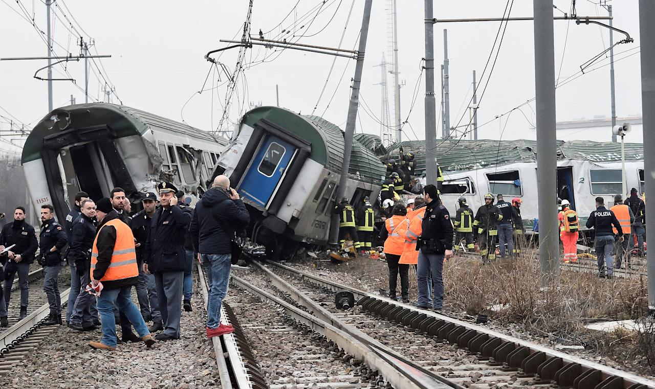 <p>Rescue workers and police officers stand near derailed trains in Pioltello, on the outskirts of Milan, Italy, Jan. 25, 2018. (Photo: Stringer/Reuters) </p>
