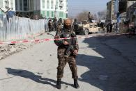 An Afghan security officer stands guard at the site of a bomb blast in Kabul